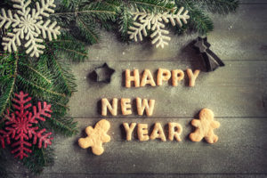 Happy New Year cookies on wooden background with blank space